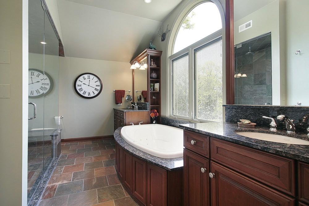 A master bathroom boasting a large walk-in shower room and a deep soaking tub by the window. The room also features a pair of sink counters with black marble countertops.