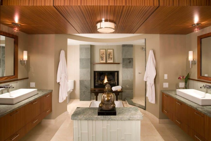Primary bathroom boasting a stunning ceiling and tiles flooring. It offers a walk-in corner shower, a toilet room, a drop-in tub with a fireplace and two floating vanities with vessel sinks.