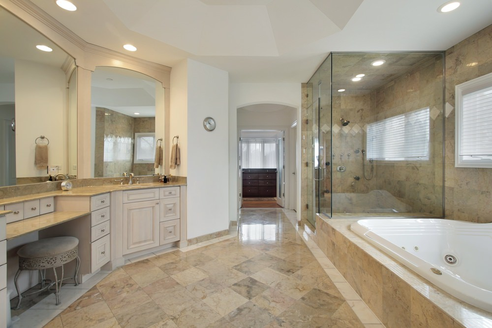Large master bathroom with a walk-in shower room, a drop-in deep soaking tub and a powder desk in between two sink counters.