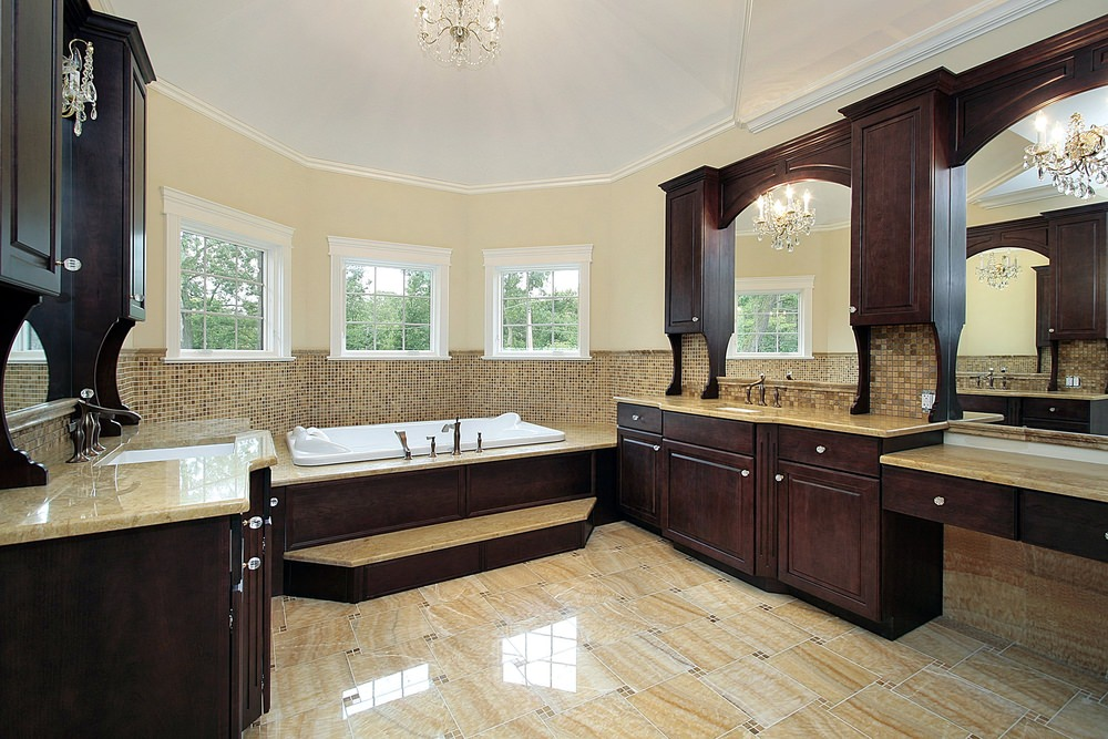 Master bathroom featuring gorgeous beige tiles flooring. The room has two marble sinks and a powder desk, along with a drop-in tub near the windows.