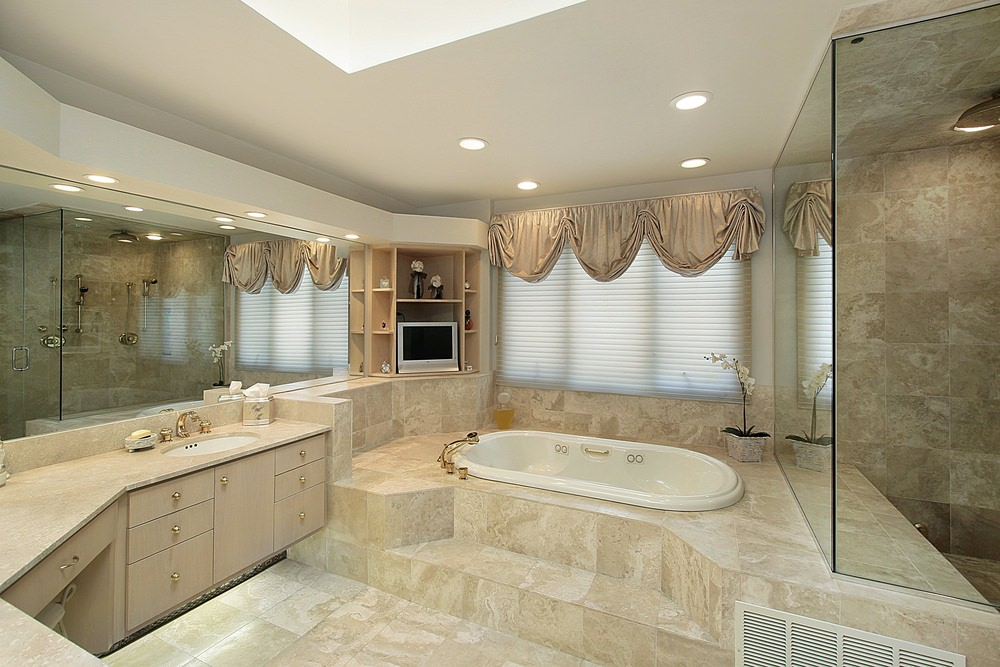 Master bathroom featuring beige tiles flooring and a white ceiling with a skylight. The room has a drop-in tub on a tiles platform and a walk-in shower room.