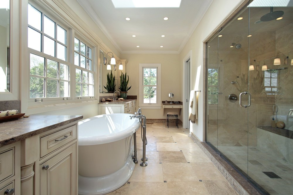 Master bathroom featuring beige tiles floors and a ceiling with recessed lights and a skylight. The room offers a large freestanding tub and a large walk-in shower room.