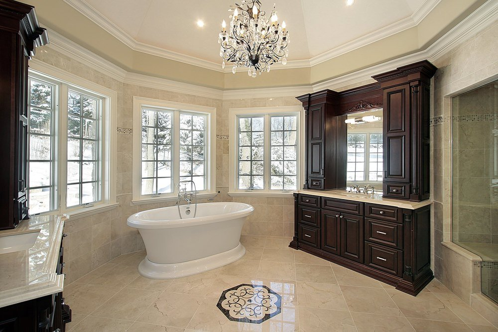 A spacious master bathroom featuring decorated beige tiles flooring and a ceiling lighted by a charming chandelier. The room offers two sink counters and a freestanding tub, along with a walk-in shower room.