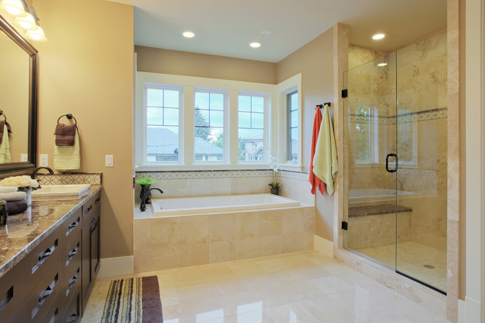 Master bathroom featuring beige tiles flooring and beige walls, along with a marble sink counter lighted by wall lights, a deep soaking tub by the windows and a walk-in shower.