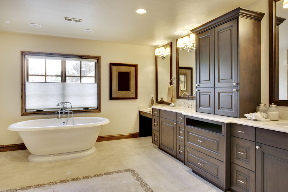 Master bathroom featuring a freestanding tub set on the decorated tiles flooring. The room offers a marble sink counter lighted by wall lights.