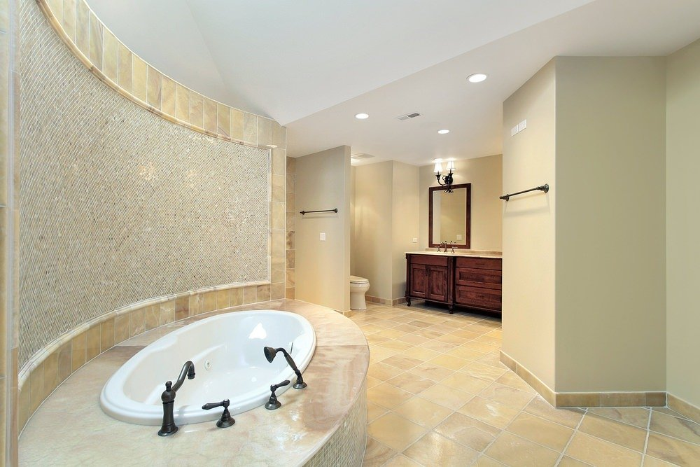 A spacious master bathroom boasting a drop-in tub set on a tiles platform and has a stunning decorated ceiling on its side.