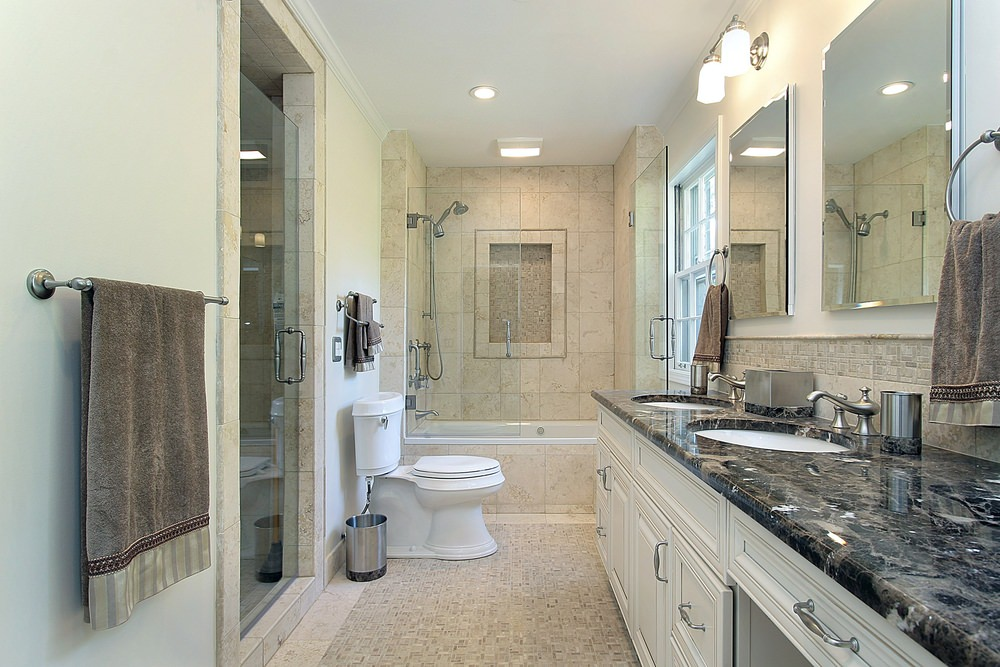 Master bathroom boasting a double sink with a stylish black marble countertop. The room offers a bathtub and shower combo, along with a separate walk-in shower room.
