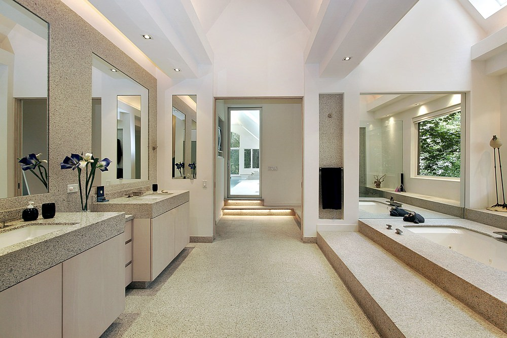 Large master bathroom with two stylish sink counters, a drop-in deep soaking tub under the ceiling's skylights and a walk-in corner shower room.
