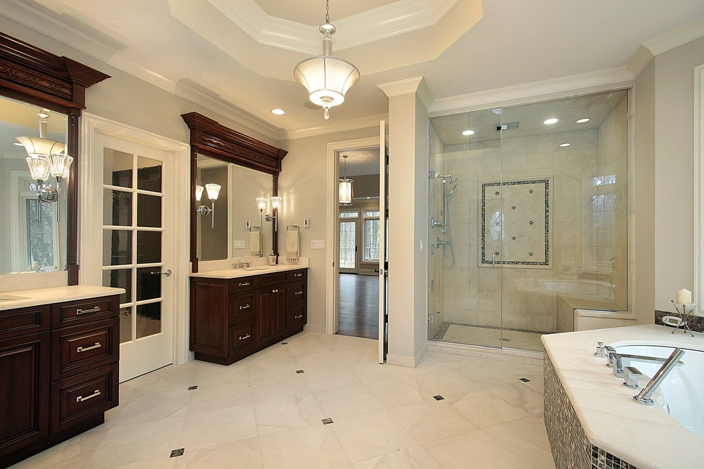 A spacious master bathroom offering two sink counters lighted by charming wall lights, along with a gorgeous tray ceiling lighted by a gorgeous pendant light. The room also offers a walk-in shower and a drop-in tub on the side.