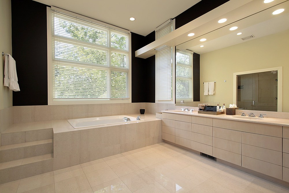 Master bathroom with beige tiles floors. It offers a drop-in tub on a nice tiles platform, along with a walk-in shower room and a marble sink counter.