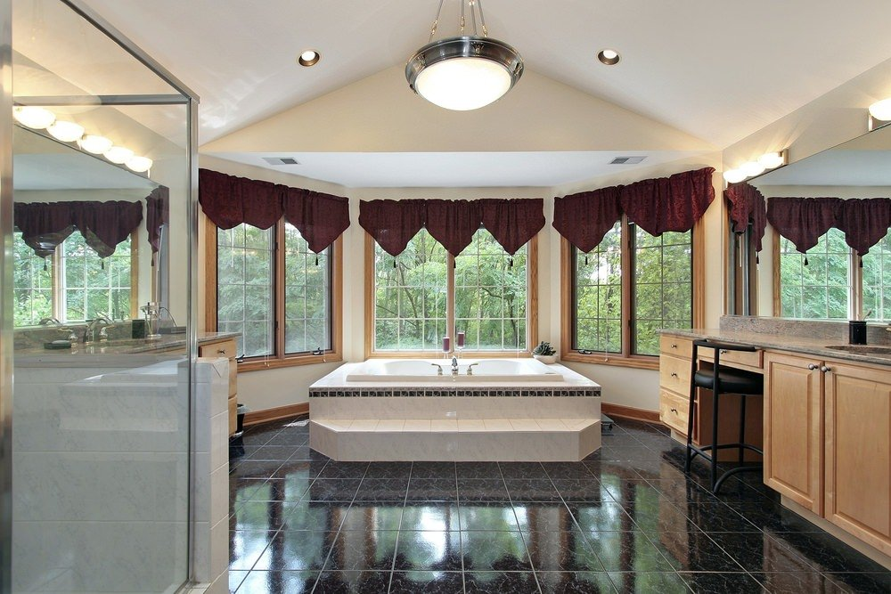 A spacious master bathroom featuring stylish black tiles flooring and a vaulted ceiling. The room offers a large drop-in tub by the windows along with granite sink counters and a walk-in shower room.