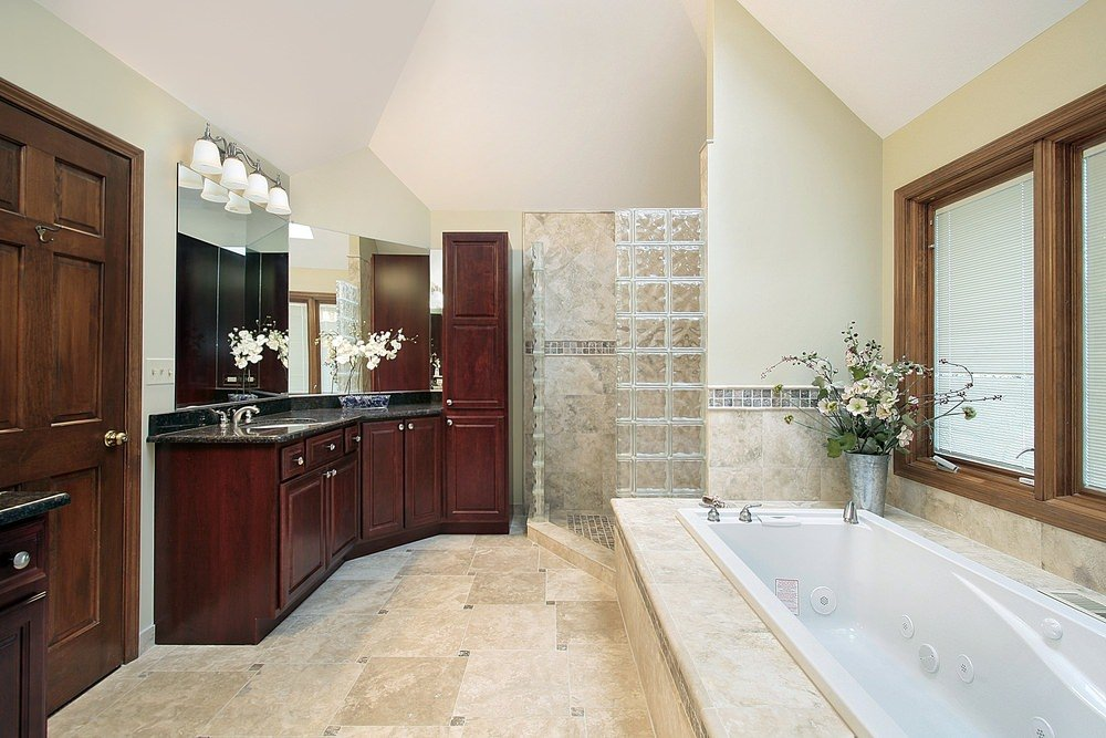 Master bathroom featuring beige tiles floors and a white ceiling. The room offers a deep soaking tub and a walk-in corner shower, along with black sink counters lighted by wall lights.