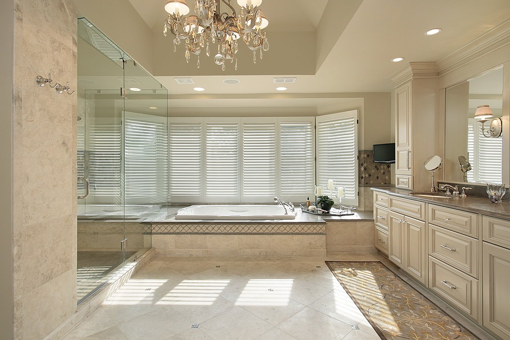 Master bathroom with beige floors and walls, along with beige cabinetry and drawers. The room offers a walk-in shower, a drop-in tub and a glamorous chandelier lighting.