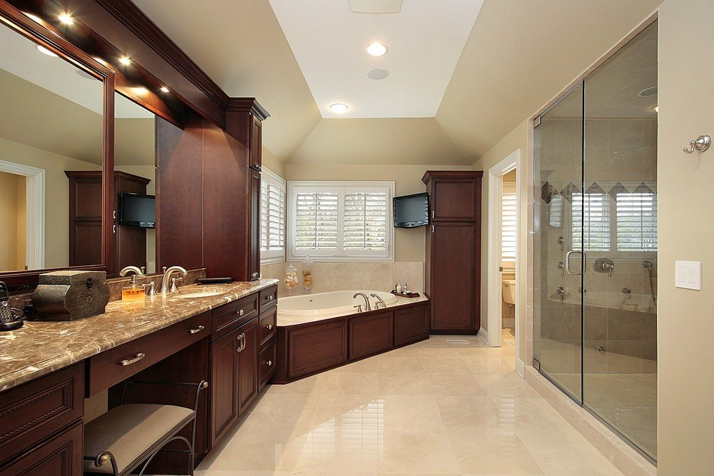 A spacious master bathroom featuring a large walk-in shower, a toilet room, a drop-in corner bathtub and a gorgeous brown marble sink counter.