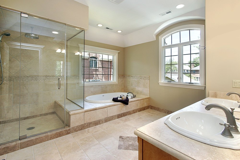 Master bathroom with decorated tiles floors. The room offers a double sink, a walk-in shower and a drop-in tub.