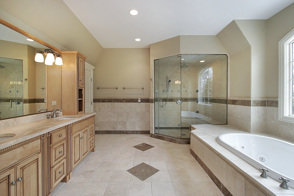 A spacious master bathroom with decorated tiles floors and walls. It offers a long sink counter with wooden cabinetry and drawers. The room also offers a drop-in deep soaking tub and a walk-in corner shower.