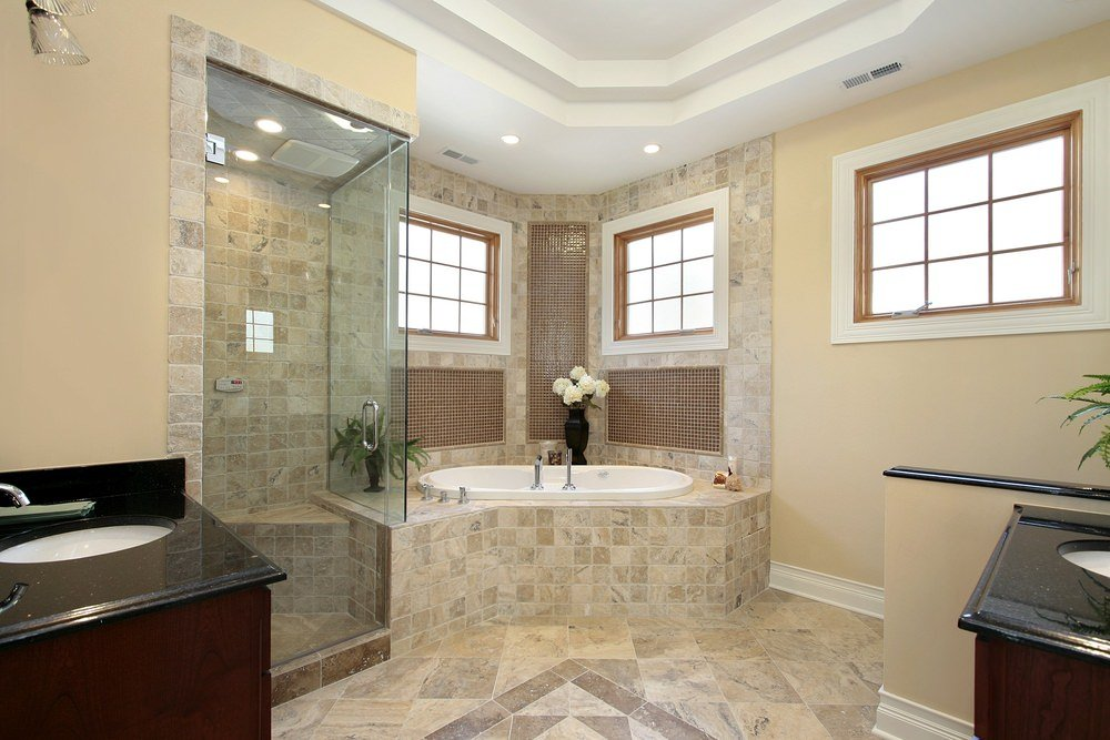 Master bathroom featuring a drop-in corner soaking tub and a walk-in corner shower room, together with two black sink counters set under the room's white tray ceiling.