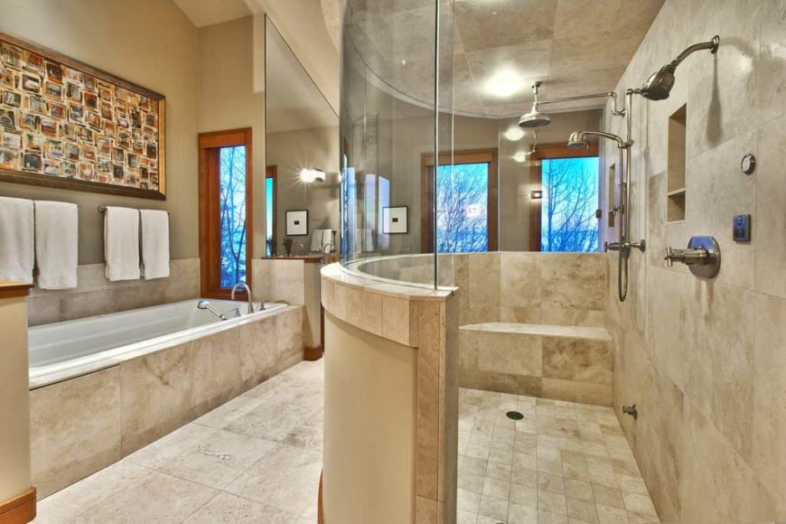 Primary bathroom featuring a spacious walk-in shower room and a deep soaking tub on the side. The room features a tall ceiling and tiles flooring.