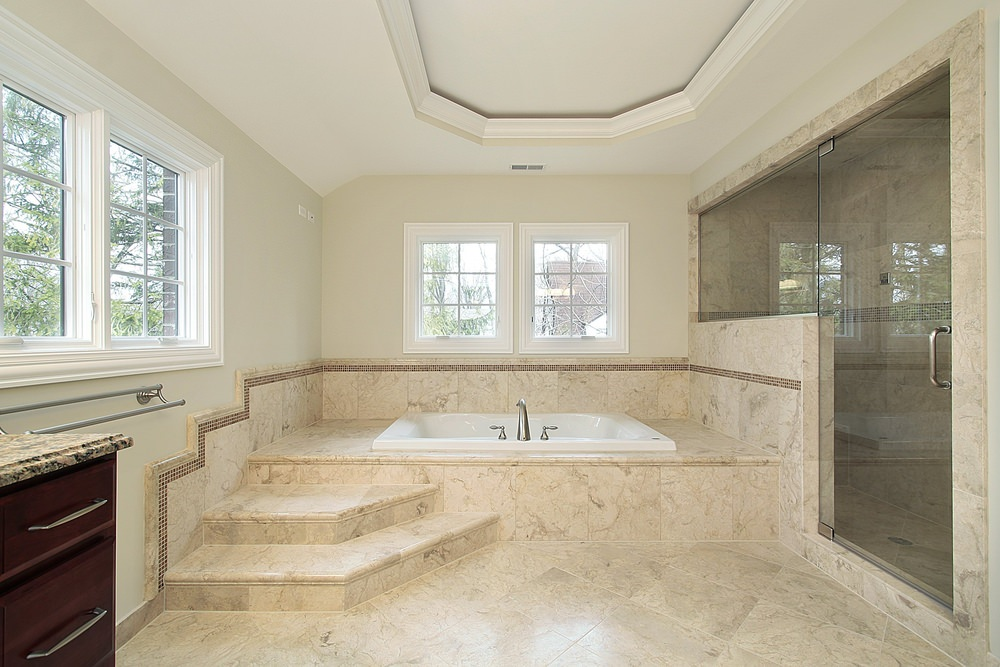 A master bathroom featuring a drop-in tub on a beige tiles platform and a large walk-in corner shower room. The room also features beige tiles floors and a tray ceiling.