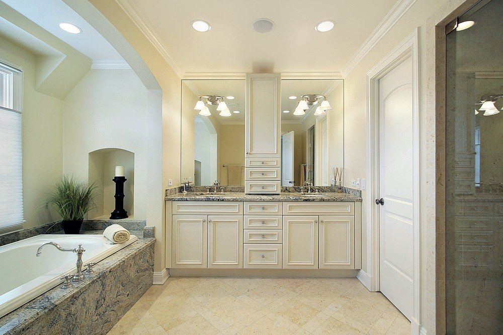 This master bathroom offers a sink counter with a gorgeous countertop matching the deep soaking tub's platform. The room also has a walk-in shower room.
