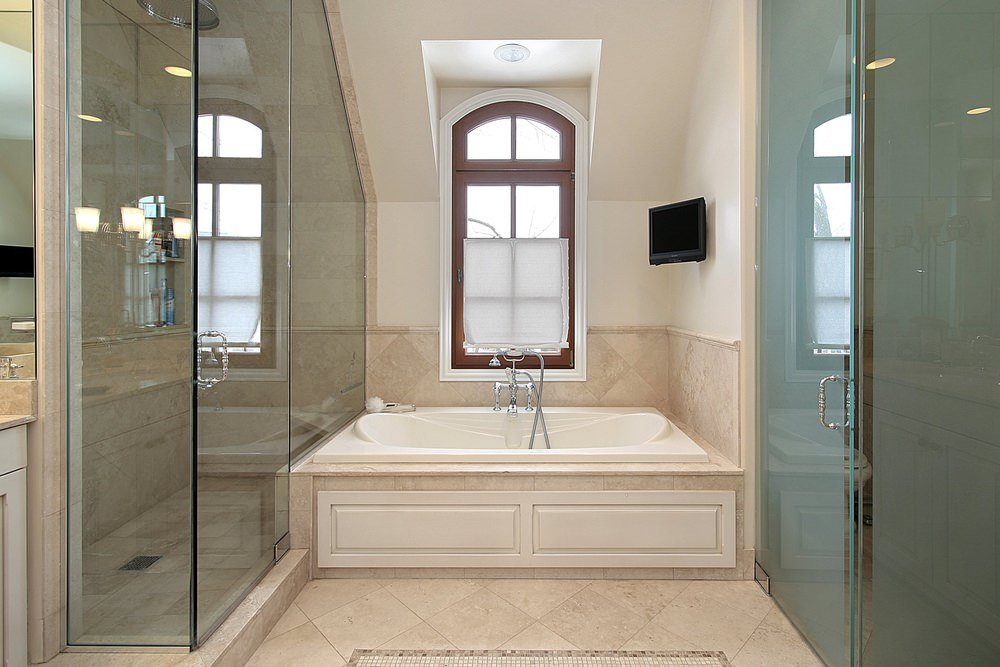 Master bathroom offering a drop-in deep soaking tub in between the room's walk-in shower room and the toilet room.
