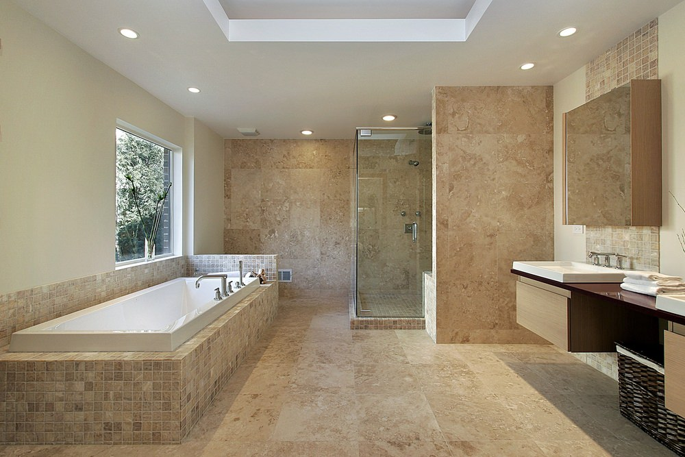 A spacious primary bathroom featuring a drop-in tub and a walk-in corner shower, along with a floating vanity with two sinks. The room also has beige tiles floors and a white tray ceiling.