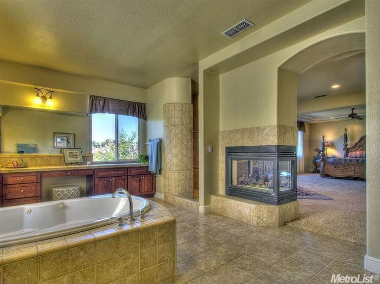 A primary suite boasting a spacious primary bathroom with a fireplace and a drop-tub in the middle. The room also offers a walk-in corner shower.