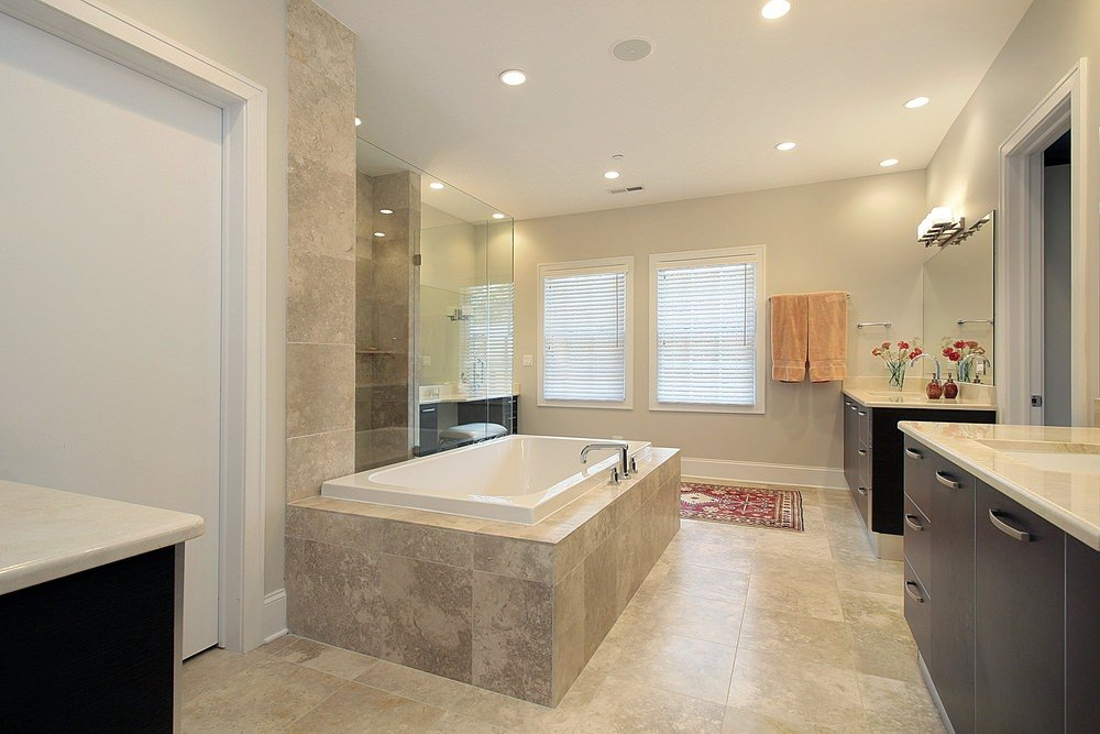 This primary bathroom boasts a well-placed drop-in tub on a tiles platform. The room has a pair of sink counters and a walk-in shower room.