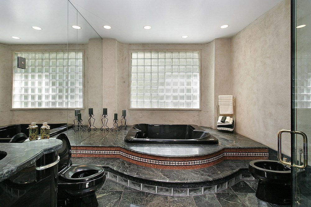 A primary bathroom boasting stunning black marble floors and sink counters, along with a black-finished drop-in tub and toilet. The room also has a walk-in shower room.