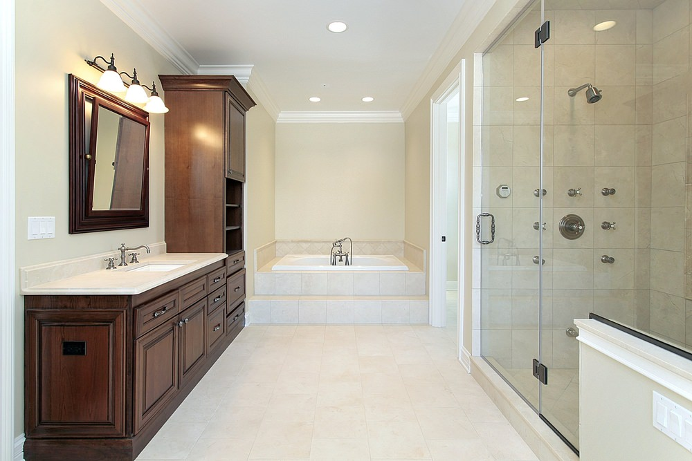 Primary bathroom featuring a single sink counter lighted by wall lights, together with a drop-in soaking tub and a walk-in shower room.