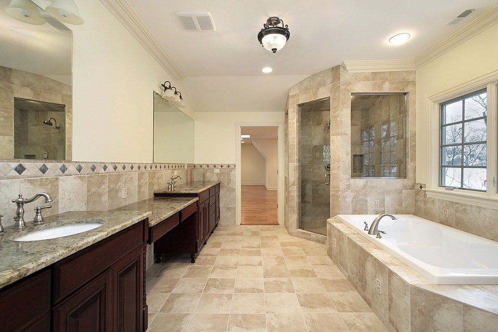 A spacious primary bathroom featuring beige tiles flooring. The room offers a walk-in corner shower room, a drop-in tub and two sink counters lighted by wall lights.
