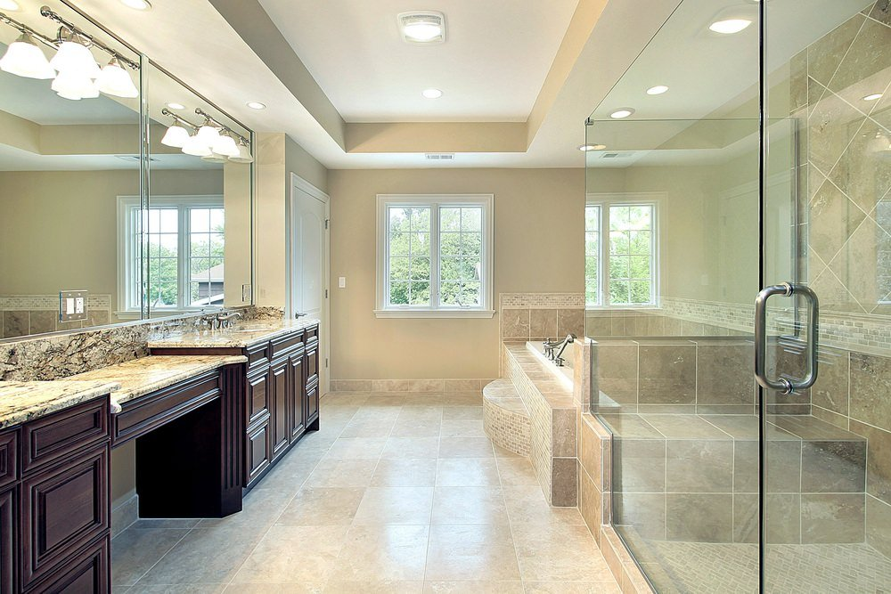 Primary bathroom featuring beige tiles floors and a tray ceiling. The room offers gorgeous marble sink counters, a drop-in soaking tub on a tiles platform and a walk-in shower room.