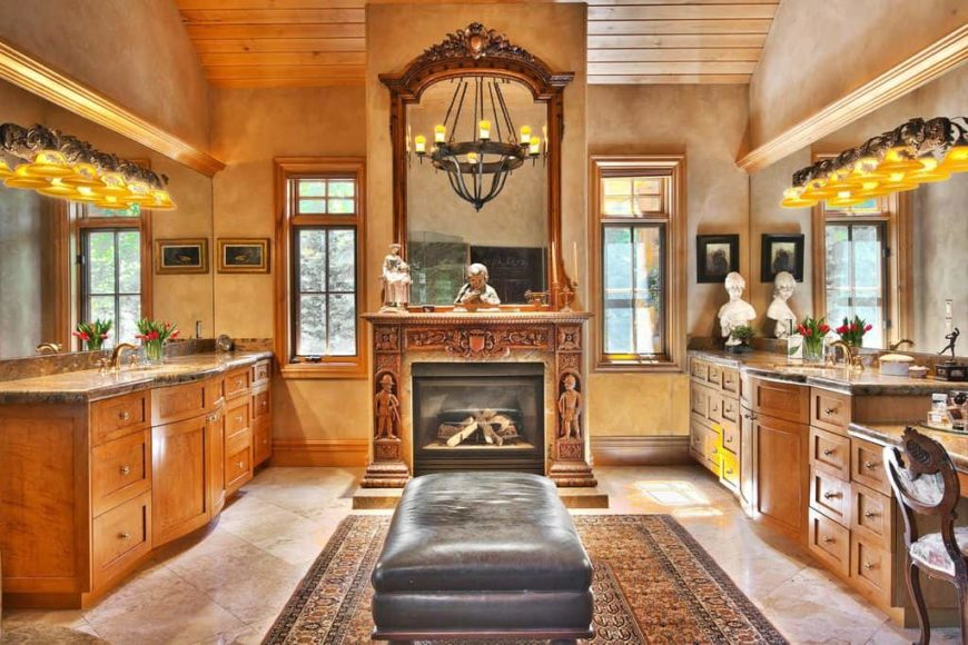 Primary bathroom featuring a tall wooden ceiling and tiles flooring. It features two sink counters, a powder area and a fireplace in the middle.