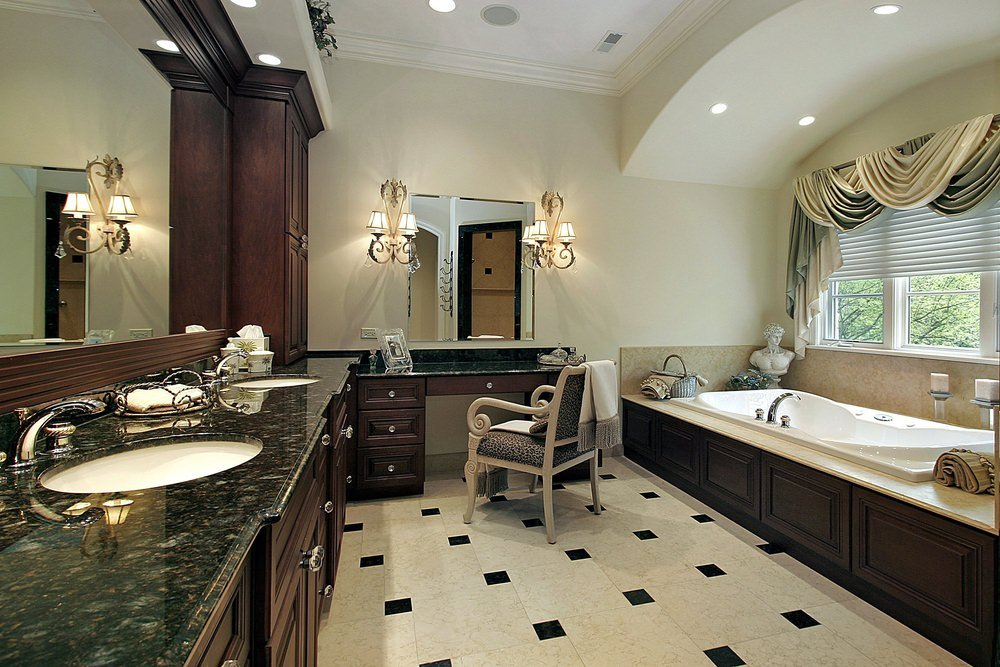 Primary bathroom offering a sink counter and a powder desk with marble countertops and lighted by gorgeous wall lights. The room also has a drop-in deep soaking tub by the windows.
