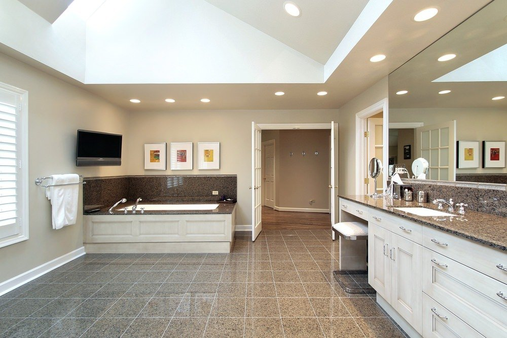 A spacious primary bathroom boasting stylish tiles floors and a tall ceiling with a skylight. The room offers a drop-in tub and a granite sink counter with a powder desk area.
