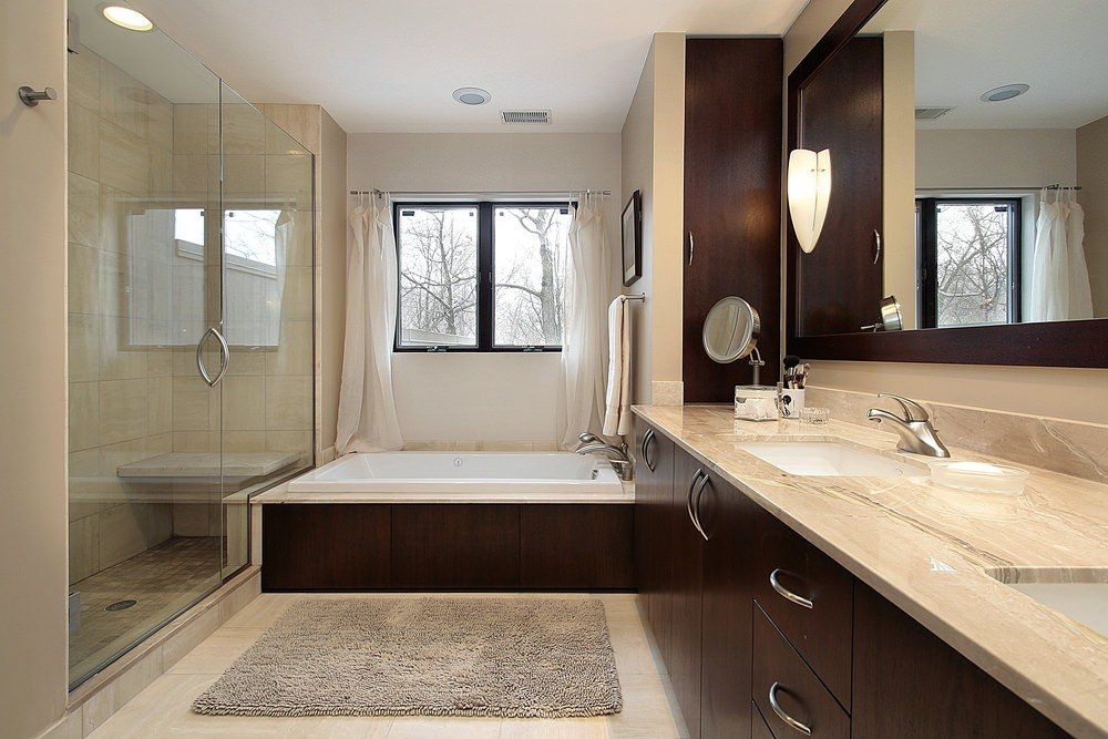 Primary bathroom featuring a walk-in shower and a drop-in soaking tub, along with a marble sink counter.