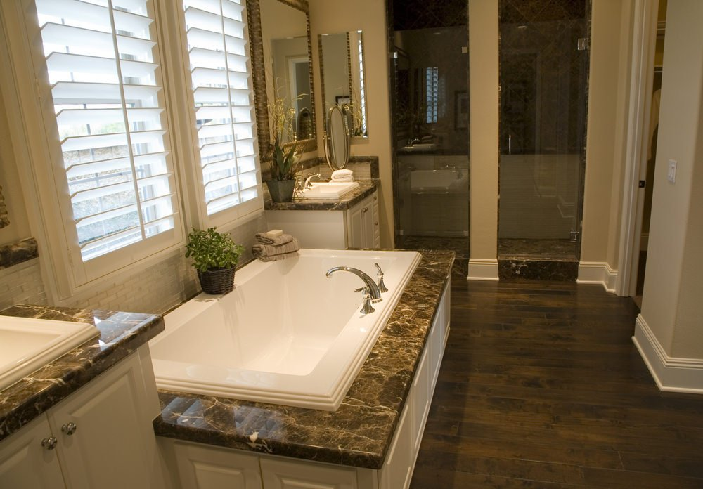 A primary bathroom boasting a walk-in shower, a toilet room and a drop-in soaking tub on a marble tiles platform.