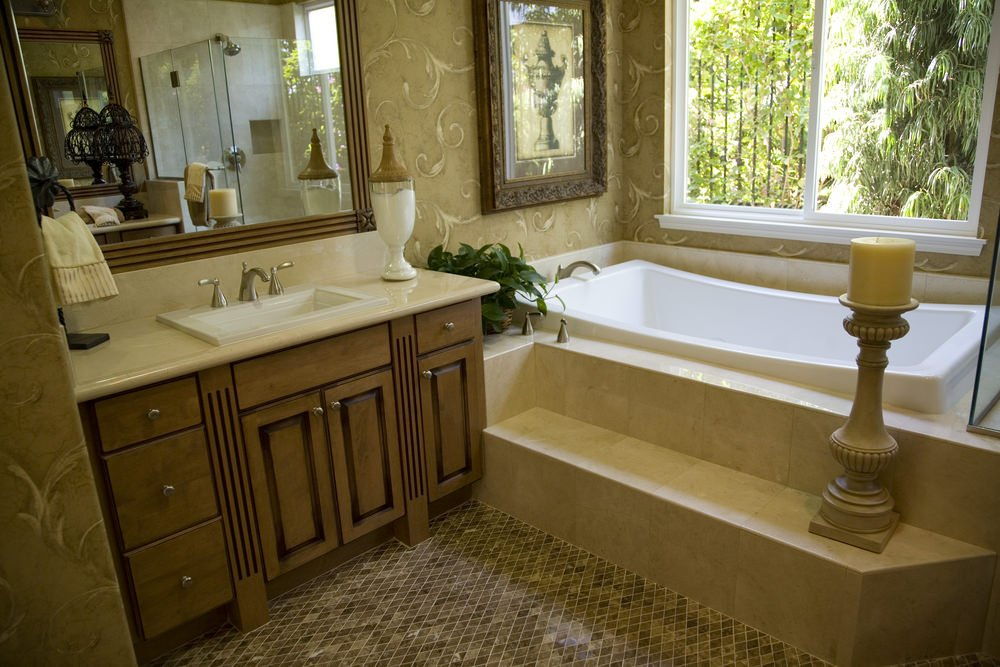 A focused shot at this primary bathroom's sink counter and drop-in deep soaking tub by the window.