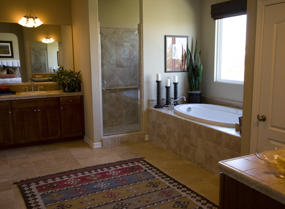 Primary bathroom featuring a drop-in tub by the window and a walk-in corner shower room, along with a sink counter lighted by classy wall lights.