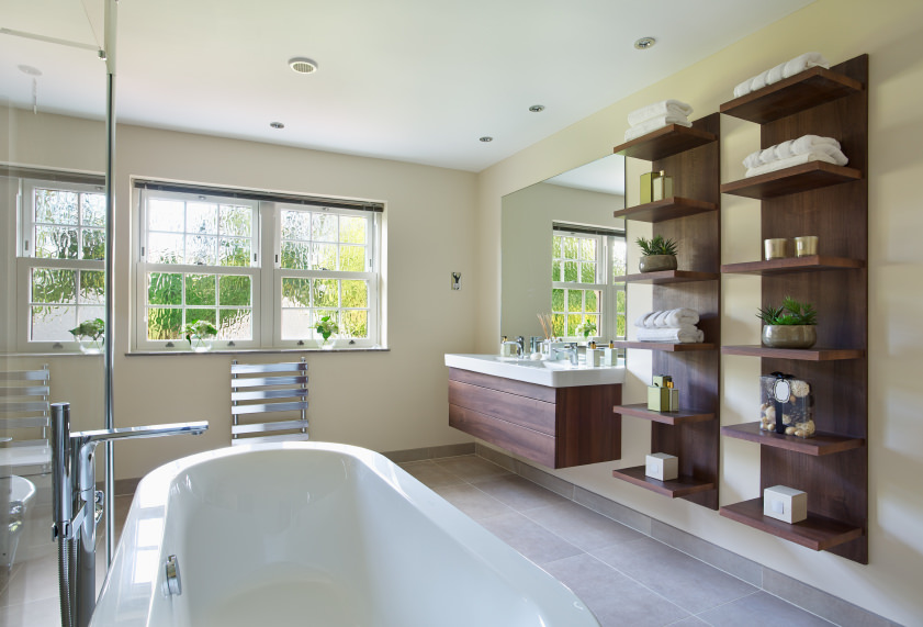 This primary bathroom offers a floating vanity, multiple built-in shelves and a freestanding tub together with a walk-in shower.