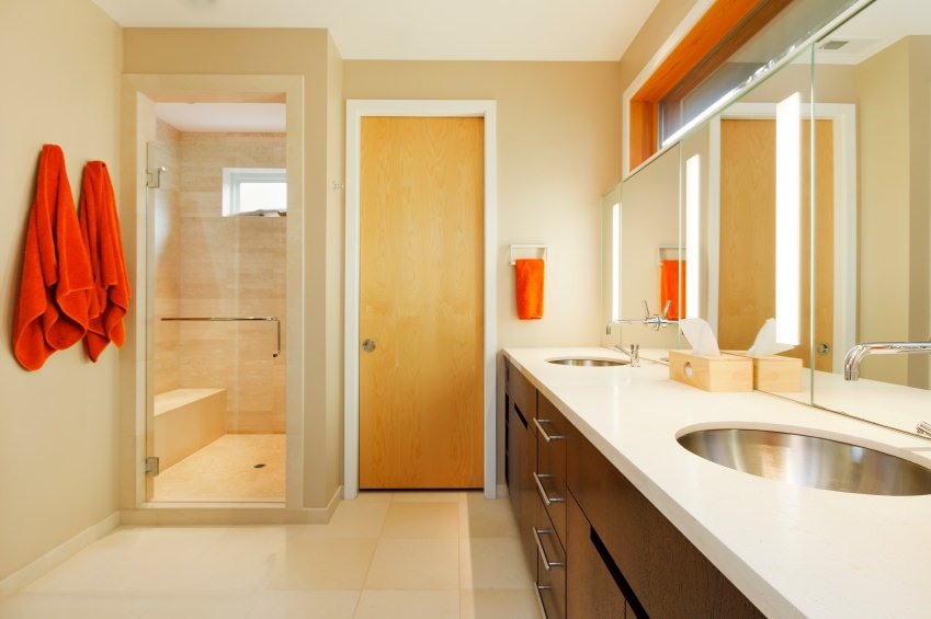 Primary bathroom offering a walk-in corner shower room, a toilet room and a white sink counter.