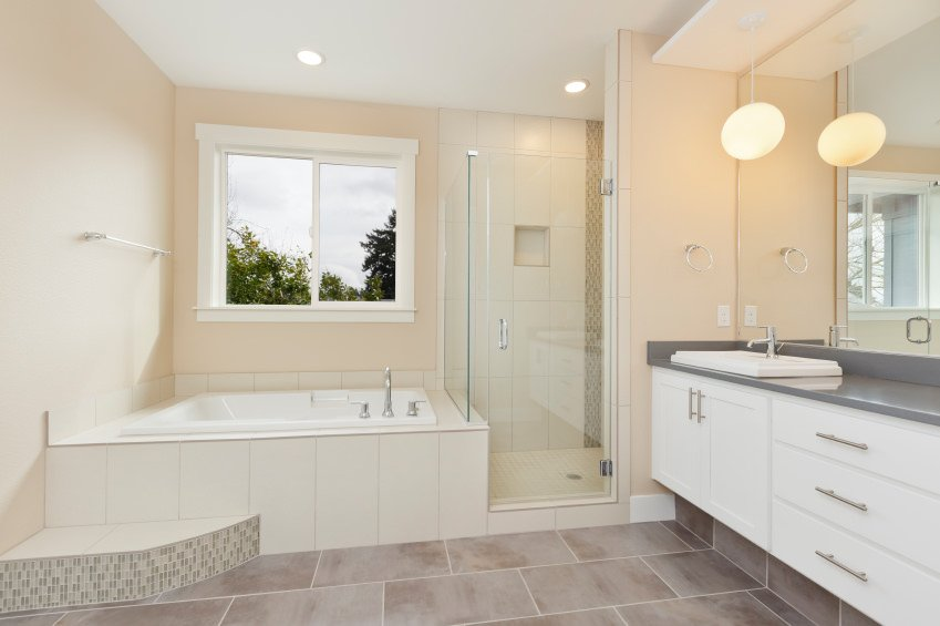 Primary bathroom featuring a drop-in deep soaking tub and a walk-in corner shower, along with a sink counter lighted by fancy pendant lights.