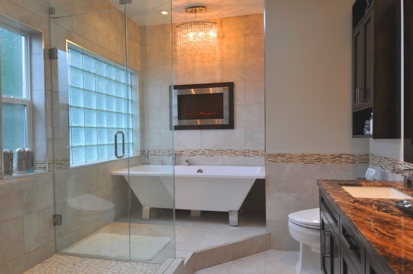 Primary bathroom offering a freestanding tub with a fireplace on the wall and has a gorgeous chandelier lighting above it. The room also offers a stylish sink counter and a walk-in shower room.