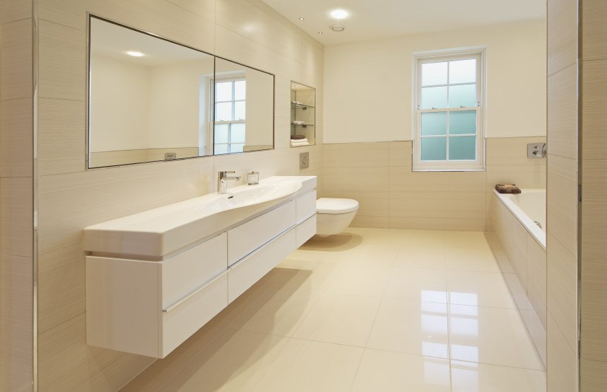 A simplistic primary bathroom offering a floating vanity and a drop-in deep soaking tub. The room features white tiles flooring.