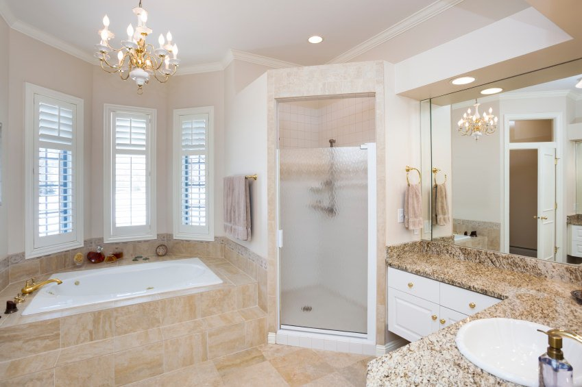 Primary bathroom offering a drop-in tub on a tiles platform along with a corner walk-in shower and a marble sink, lighted by a charming chandelier.