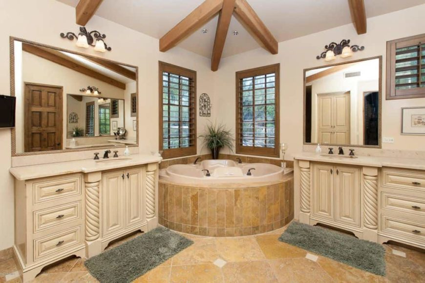 A spacious primary bathroom featuring a stunning corner tub along with two sinks lighted by classy wall lights. The room has tiles flooring and a ceiling with exposed beams.