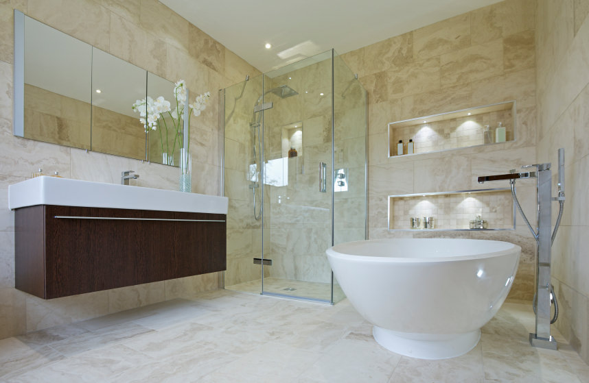 A primary bathroom offering a floating vanity, a freestanding tub and a walk-in shower surrounded by decorated walls with built-in shelving.