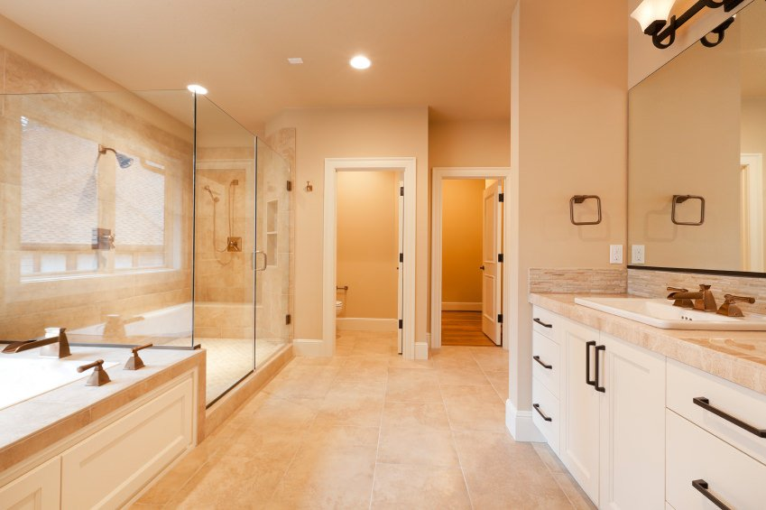 Spacious primary bathroom with beige walls and floors. IT offers a large walk-in shower room and a drop-in soaking tub, along with a toilet room.