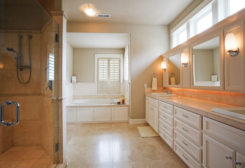 Master bathroom featuring a walk-in shower, a drop-in soaking tub and a long sink counter lighted by wall lights.