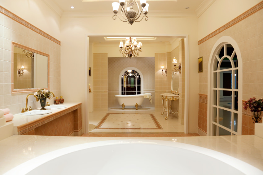 A spacious master bathroom boasting a freestanding tub on the other side of the room, along with a classy double sink. The room boasts elegantly decorated floors and a ceiling with charming chandelier lights.